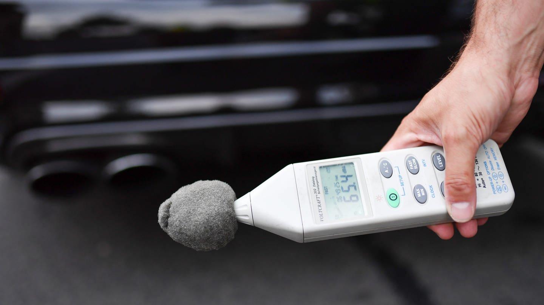 Dezibel-Messgerät vor einem Autoauspuff (Foto: picture-alliance / Reportdienste, picture alliance / Uwe Anspach/dpa)